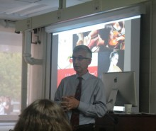Prof. Domenico Teker presents in front of a PowerPoint.